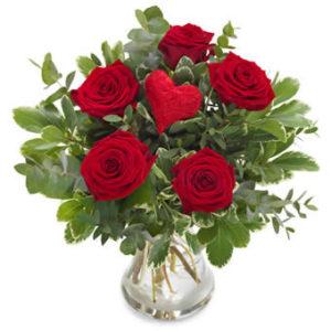 Bukett med röda rosor och ett rött dekorationshjärta