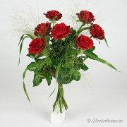 Sju mörkröda rosor tillsammans med fontängräs.