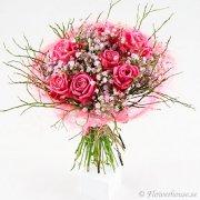 Bukett med rosa rosor, vit brudslöja och blåbärsris.