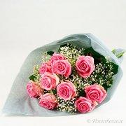 Bukett med rosa rosor och vit brudslöja, inslagen i fint silkespapper.