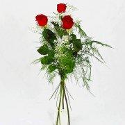 Tre röda rosor tillsammans med vit brudslöja.